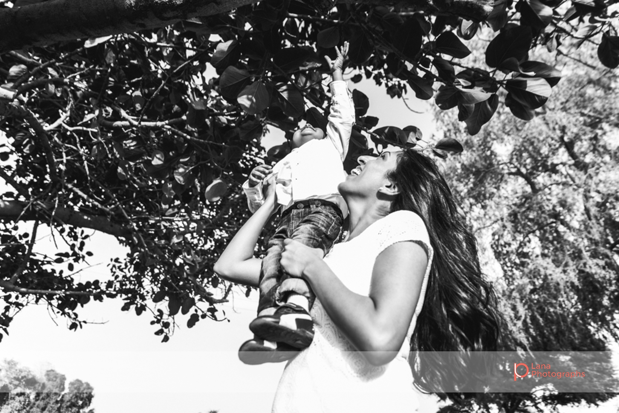 Lana Photographs Family Photographer Dubai Top Family Photographers mother with long black hair carrying her child under a tree