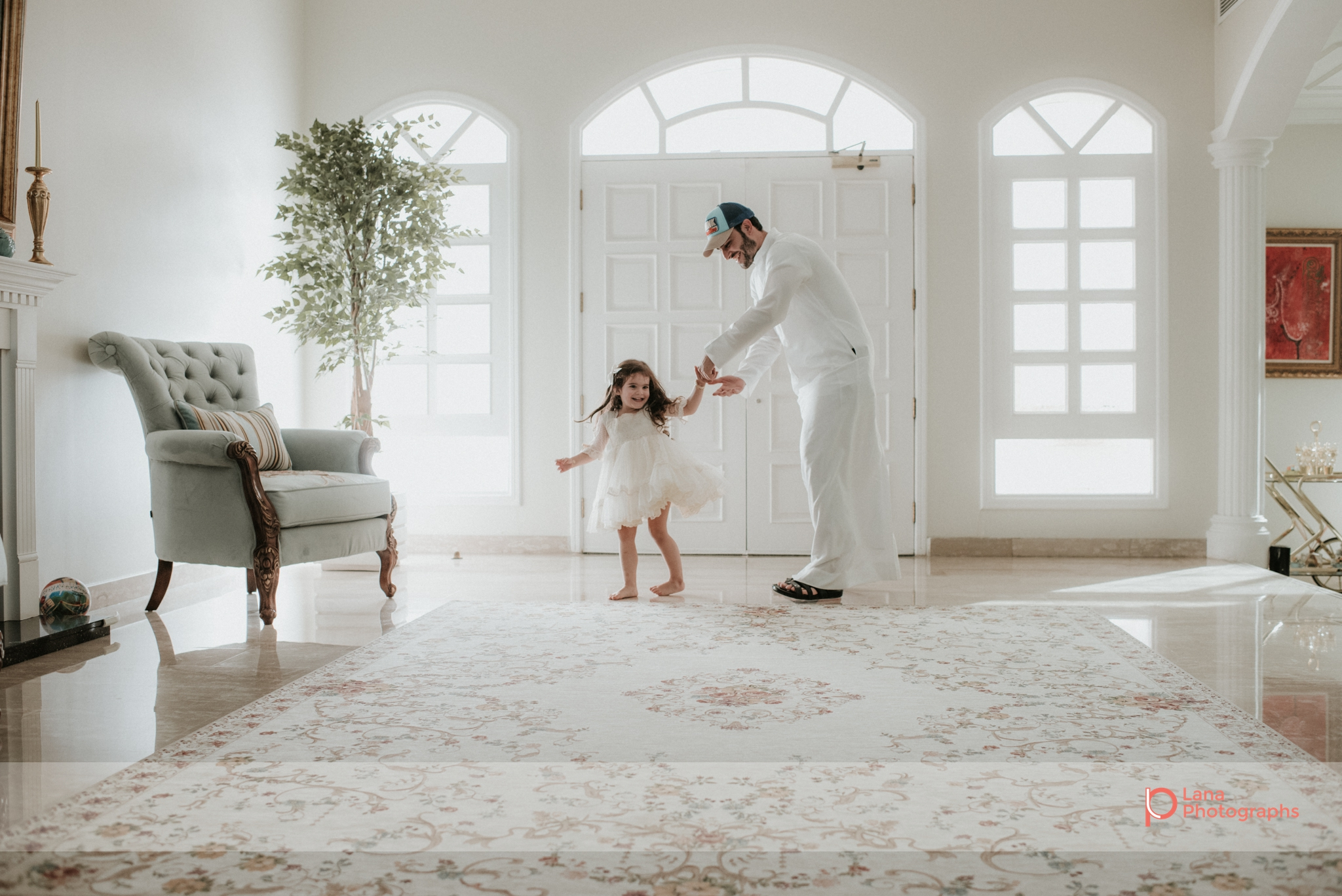 Lana Photographs Family Photographer Dubai Top Family Photographers father twirling his daughter