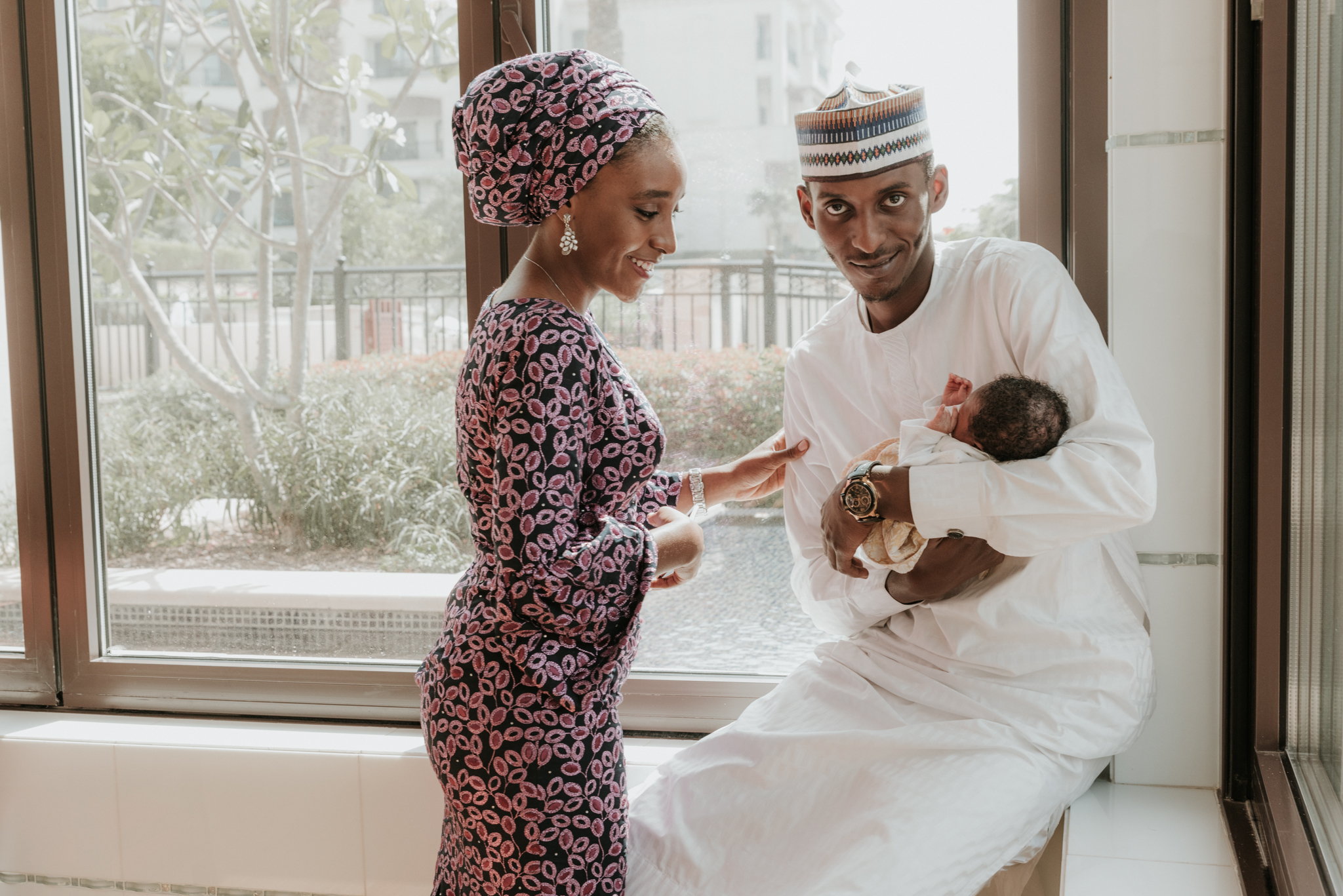 Lana Photographs Newborn Baby Photographer Newborn Photographer Dubai Professional Newborn Photography portrait of a father holding his newborn child by the window