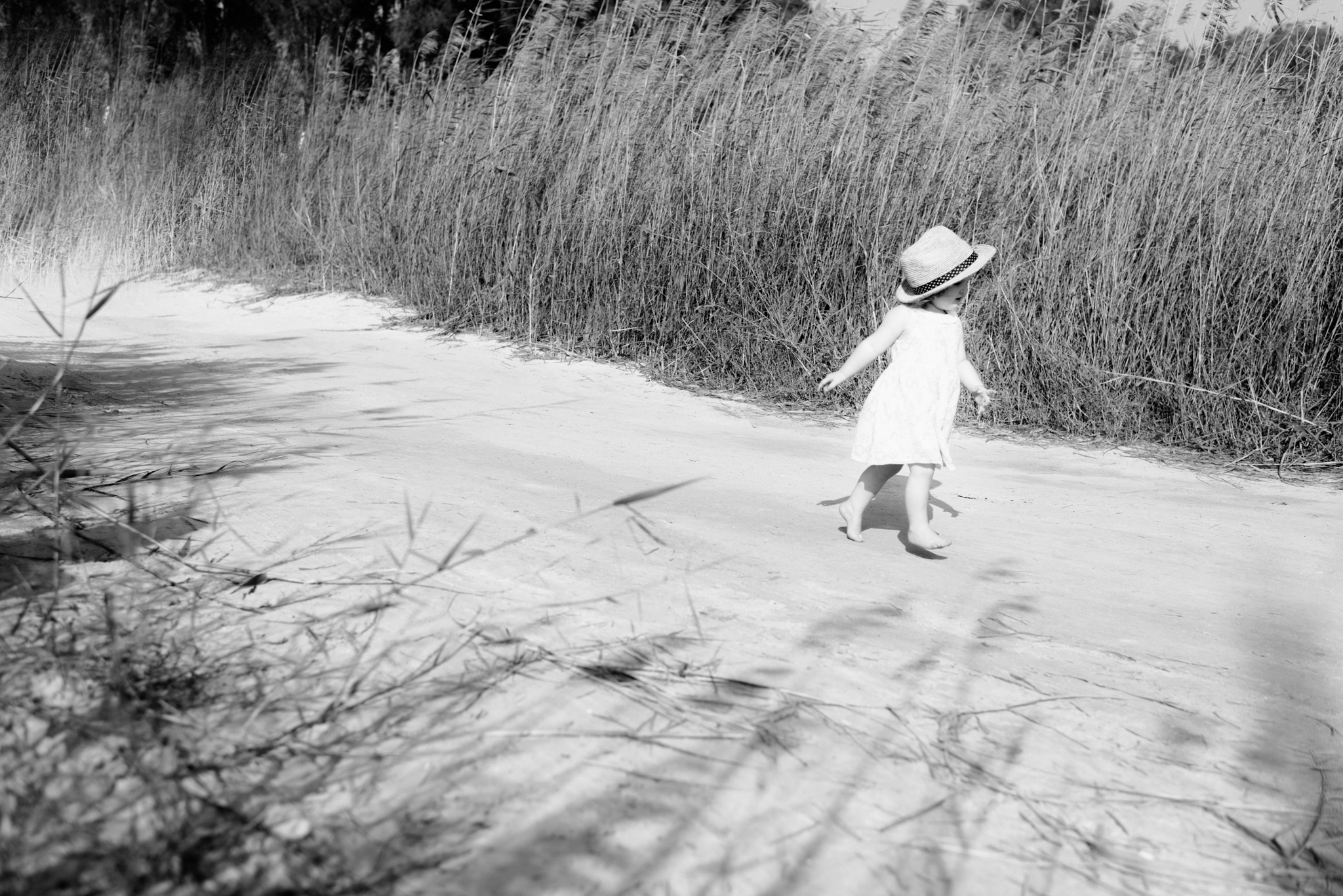 Lana Photographs Family Photographer Dubai Top Family Photographers portrait of a little girl in a sundress wearing a hat and running between wild bushes near the sea