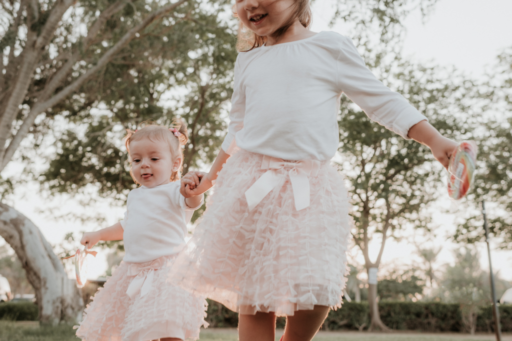 Lana Photographs Dubai Family Photographer two girls in pink tutus running holding hands