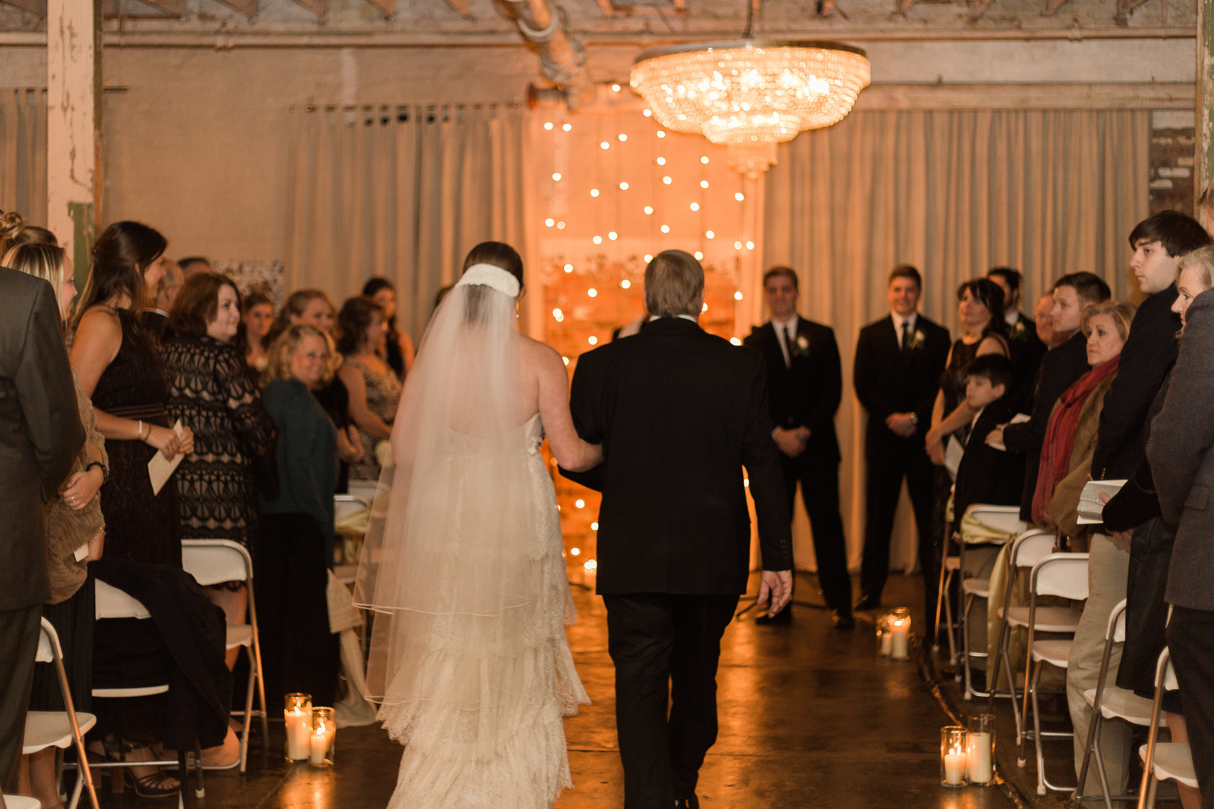 the bride makes her entrance down a romantic aisle styled with candles and lighting on the exposed brick backdrop.