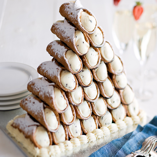 you don't have to be italian to appreciate a cannoli tower. these delicious hand helds will leave a lasting impression with all of your guests. - Image Credit: Wedding Elation