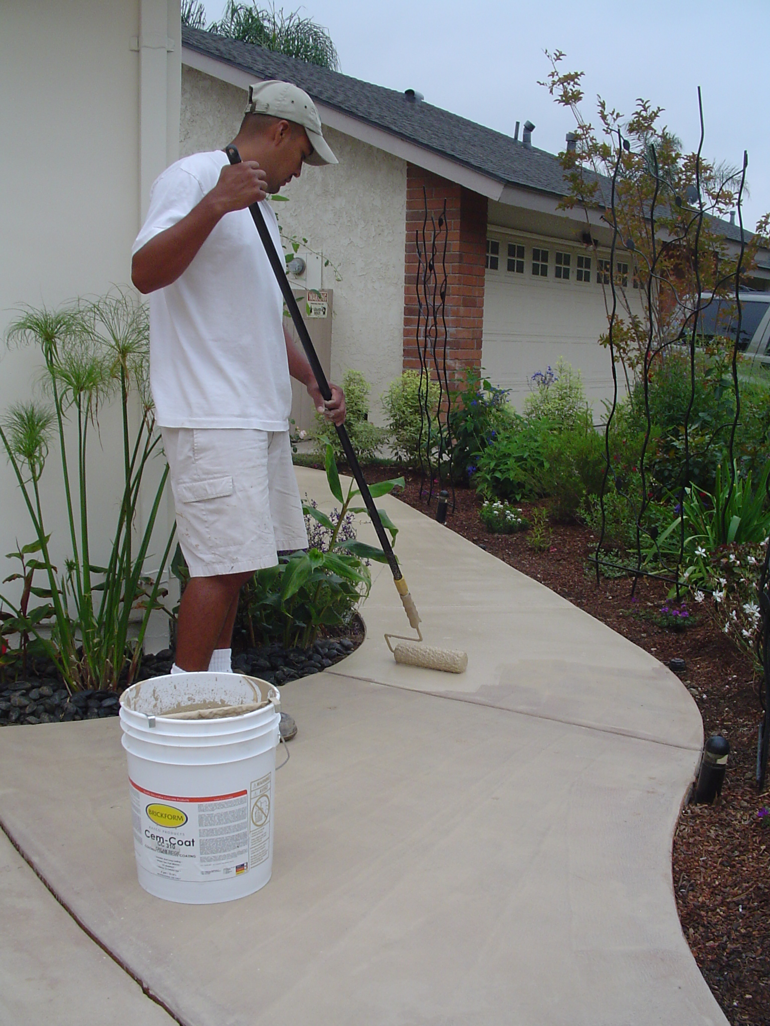 Cem-Coat is being applied to restore a blotchy driveway and sidewalk combination.
