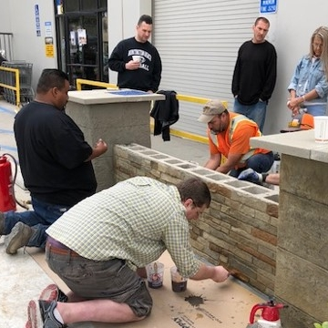 Students apply water based stain to the textured and carved vertical surface.