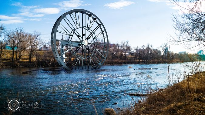 """RiNo landowner's forecast calls for 50 percent chance of huge water wheel  """"The proposal is to build a 50-foot wheel that would spin with the river's flow. Its backers say it could provide renewable power to the RiNo Promenade, a mile-long park set for construction along  the banks of the river.  A separate, floating component would be anchored in the river to collect trash and prevent debris from entering the wheel.""""   8/16/18 Denverite"""