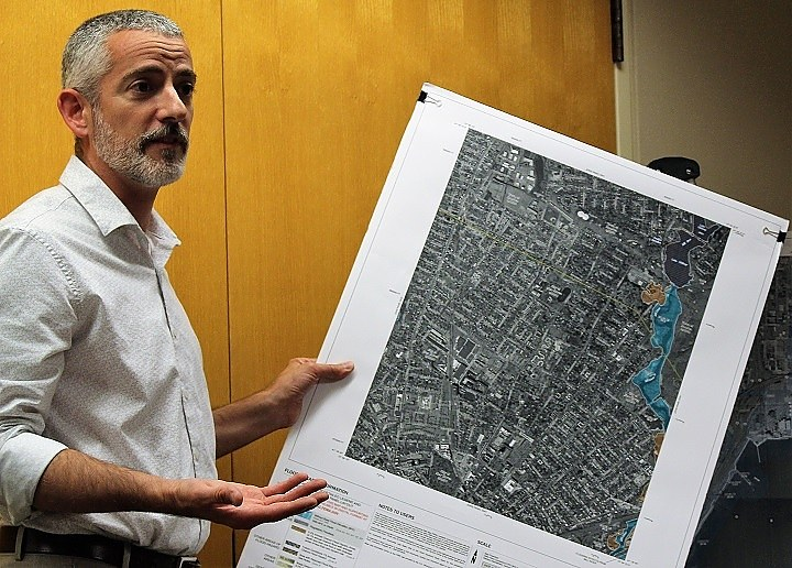Water resources consultant Murphy with a FEMA Flood Insurance Rate Map (FIRM) of downtown New Haven.