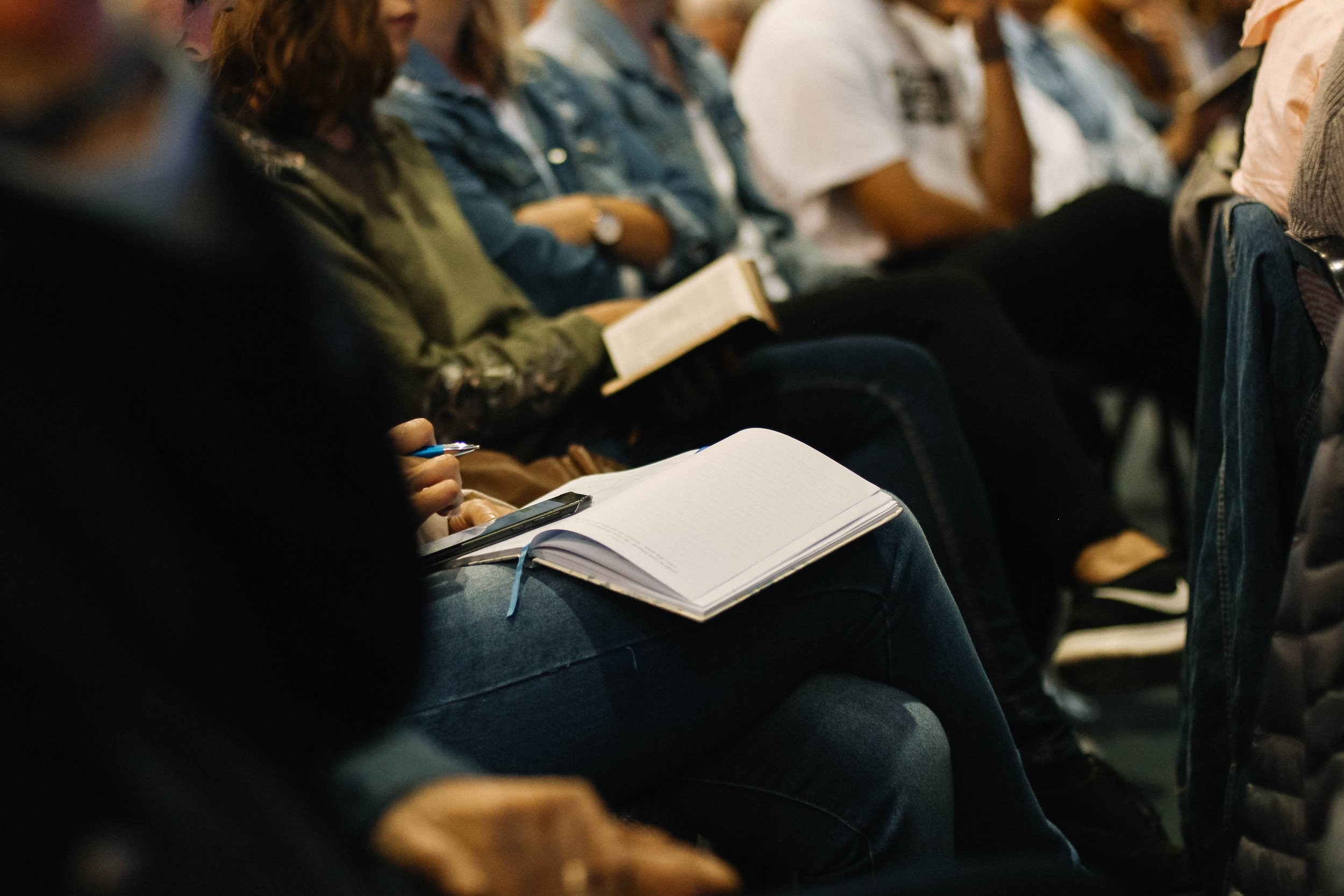 Evidence-Based Mindfulness for College Students Image Depicting Students at a Lecture Taking Notes in Notebooks