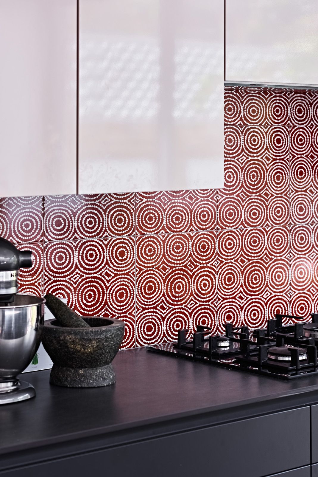 Our award-winning Bush Onion 1 ceramic wall tile  as a kitchen splash back, adding a subtle element of ochre red & geometry to the clean lines of this contemporary minimalist kitchen design, creating a space with a unique elegance and simplicity.