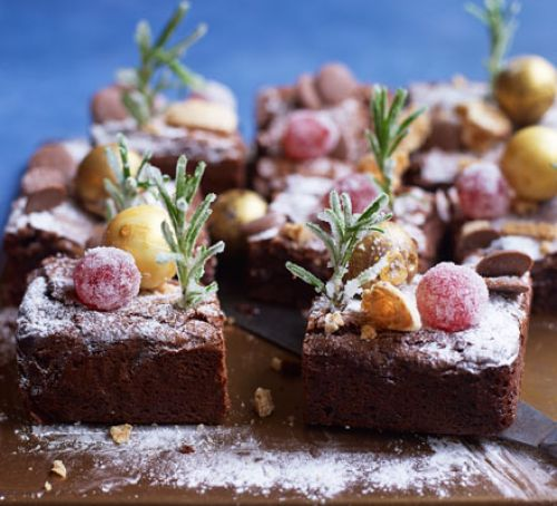 Ingeredients:  200g unsalted butter cut into cubes, plus extra for greasing, 100g dark chocolate, chopped, 100g milk chocolate, chopped, 3 large eggs, 300g golden caster sugar, 100g plain flour, 50g cocoa powder, ½ tsp mixed spice  For decorating:  rosemary, glacé cherries, 1 egg white, caster sugar, 4 amaretti biscuits, crushed, 9 chocolate truffles,1-2 tsp icing sugar for dusting, chocolate button, edible silver balls