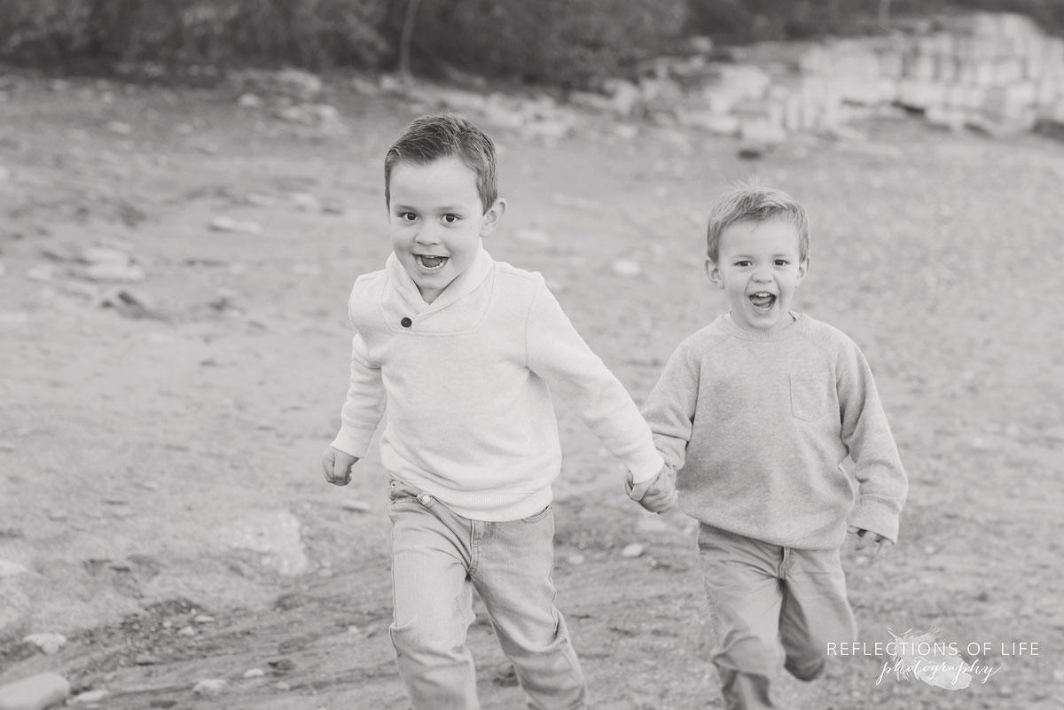 little boys running on the beach in niagara region of ontario canada