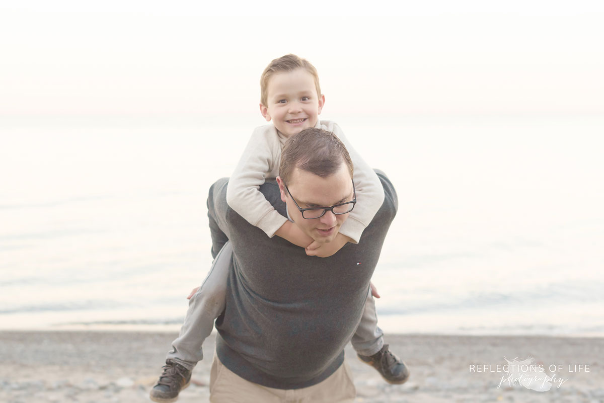 little boy playing with dad on the sandy beach in southern ontario canada