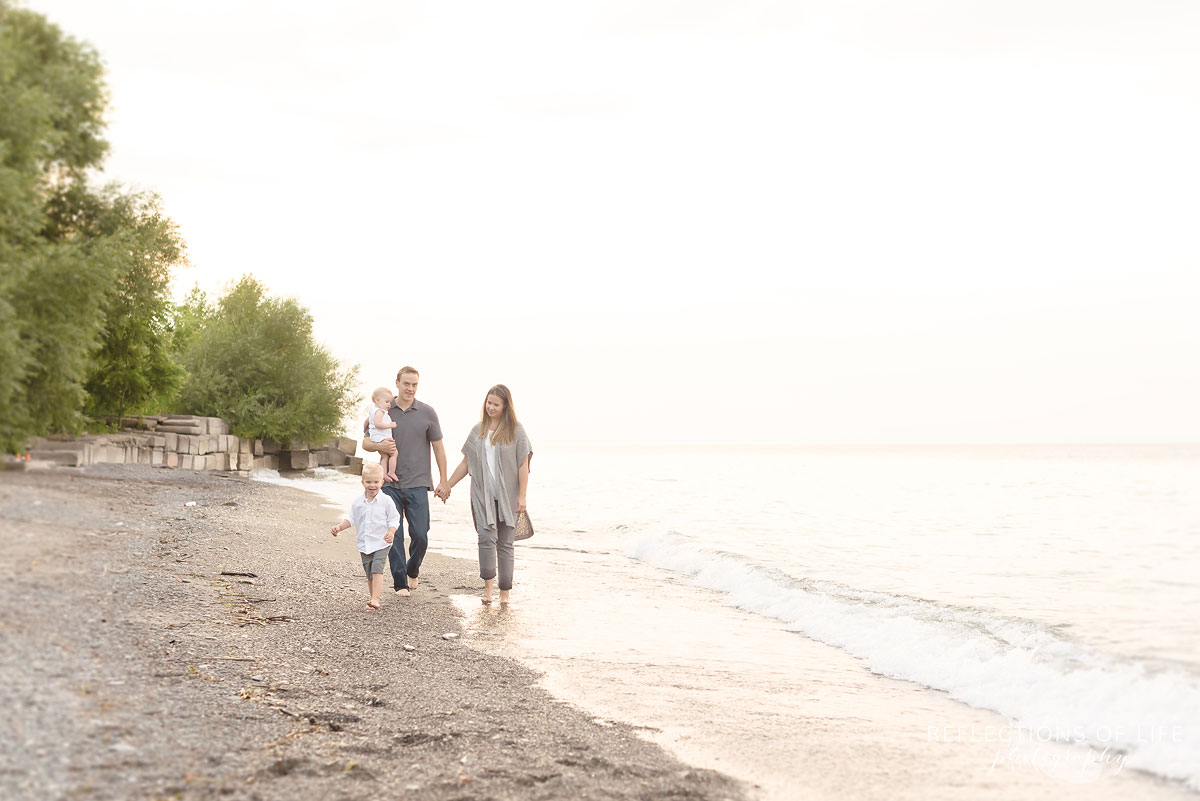 019 family walking down the beach with waves in Grimsby Ontario