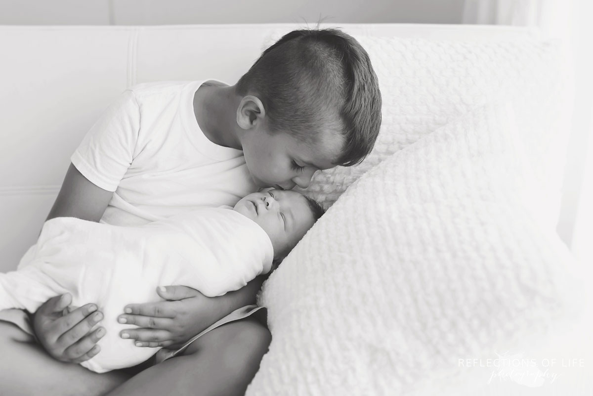 Black and white of boy cousin holding his new baby boy cousin in his arms in baby photography studio