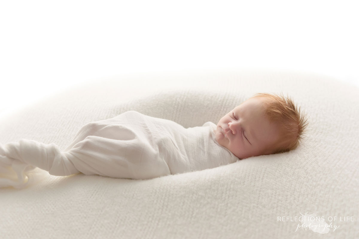 Natural light newborn baby photography of redhead swaddled in white