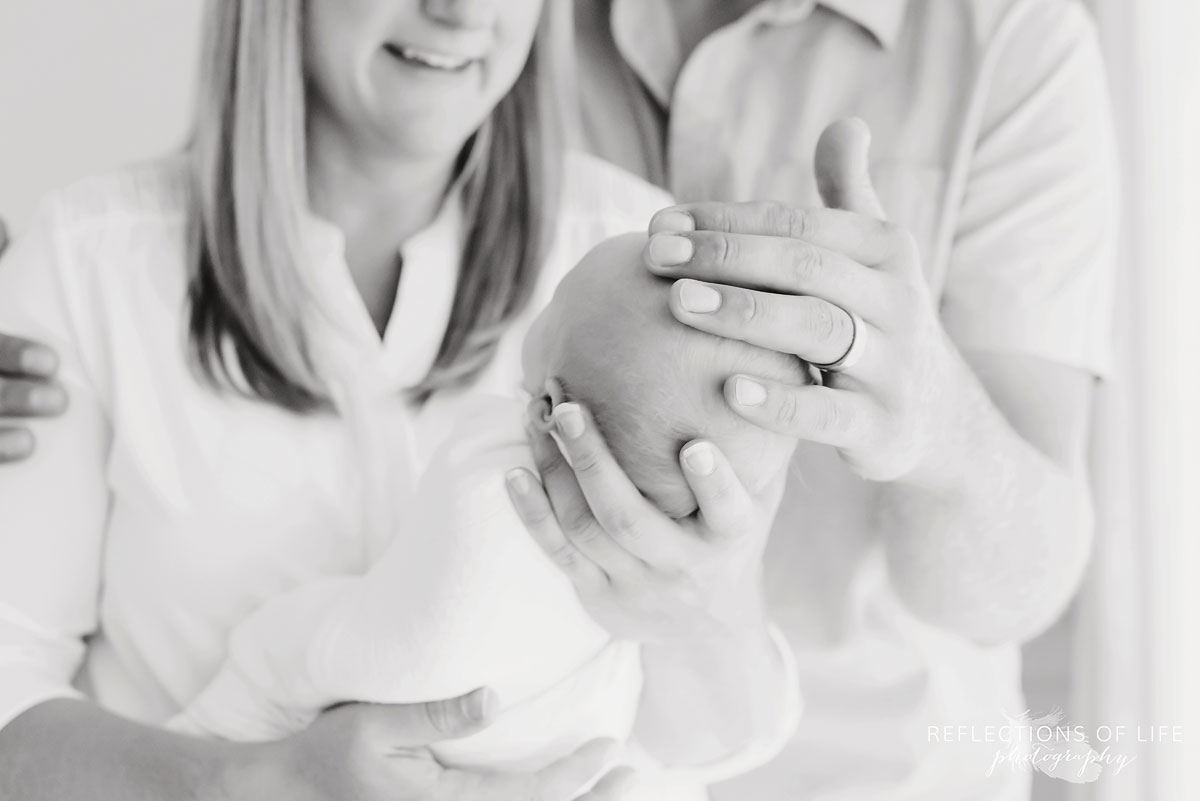 Beautiful portrait of mom and dad holding newborn baby boy