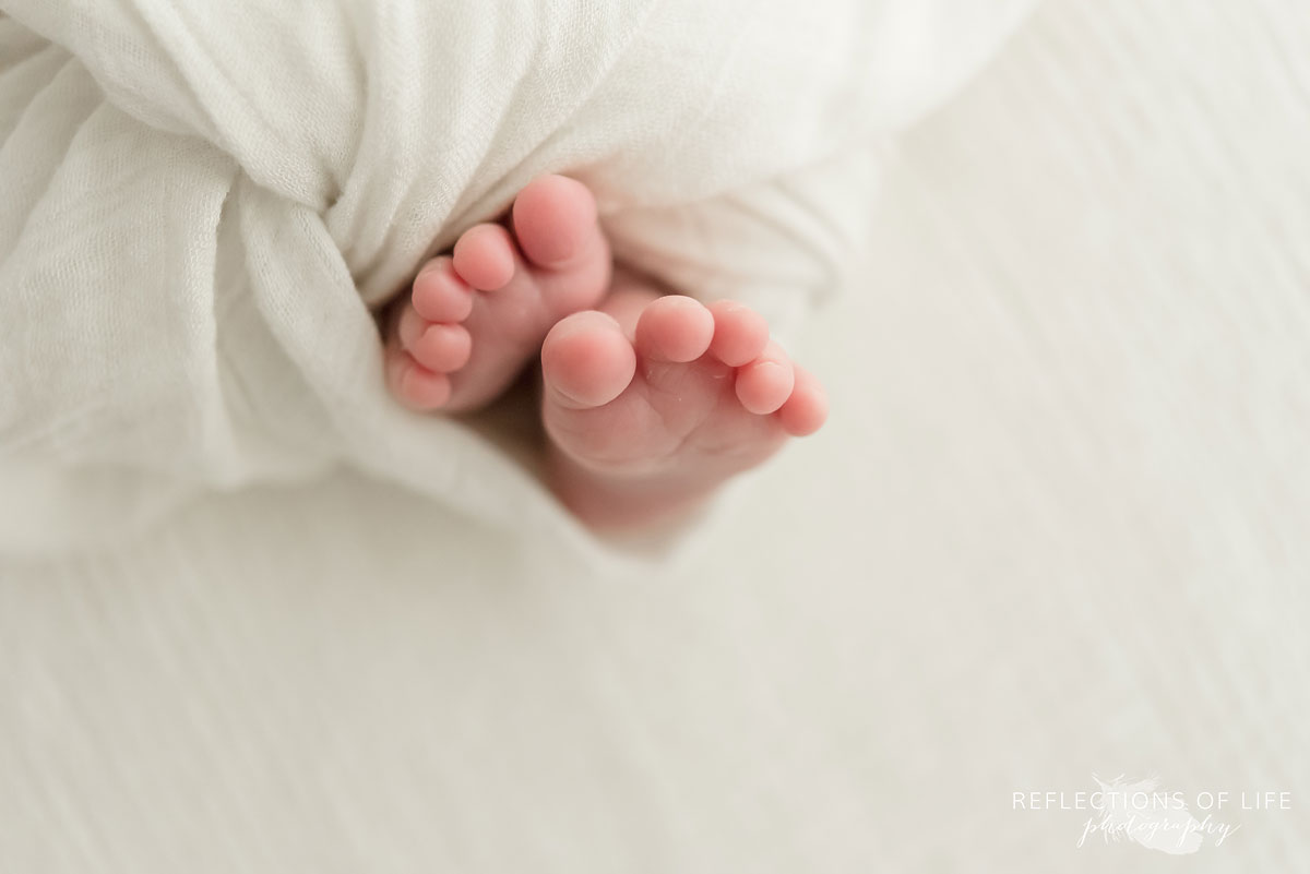 Adorable baby feet wrapped in white blanket