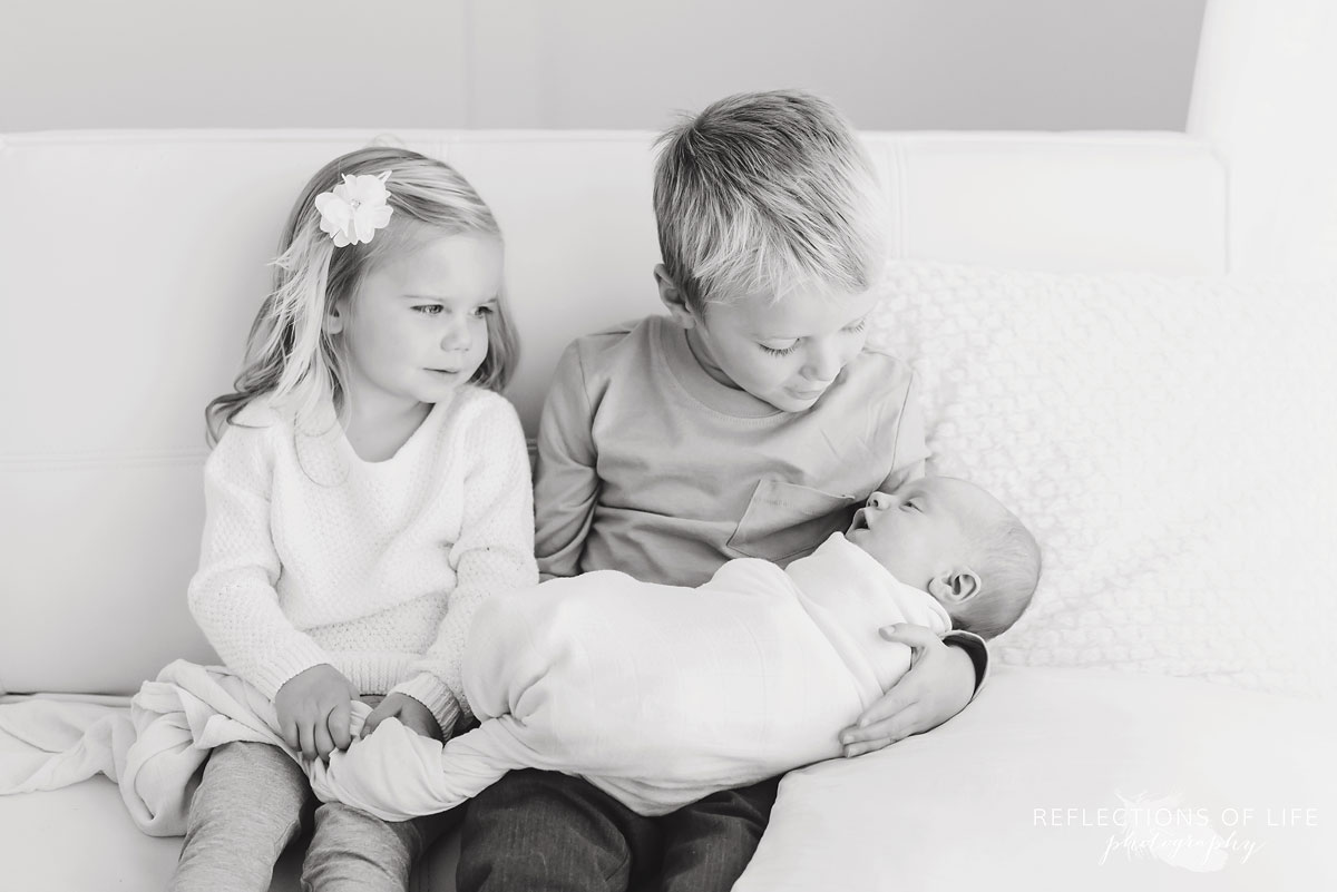 Black and white photo of siblings looking down at their newborn baby sister