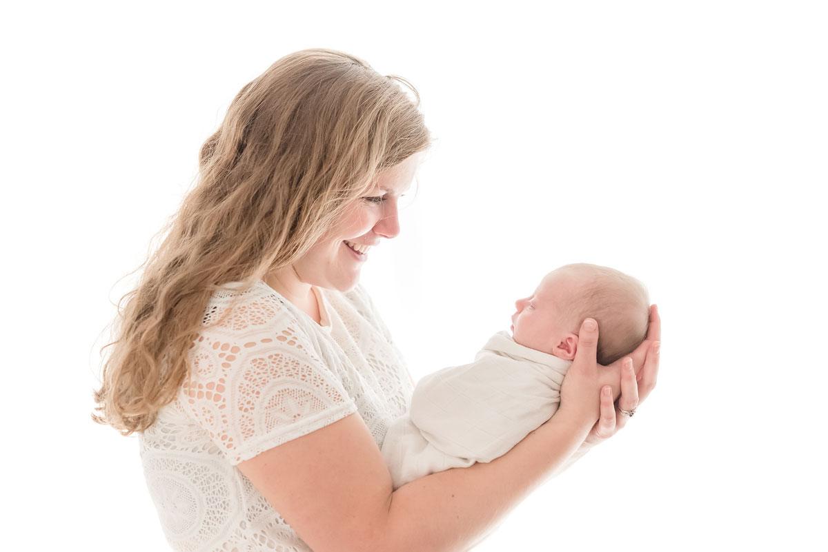 Proud mama holding her newborn baby backlit in studio