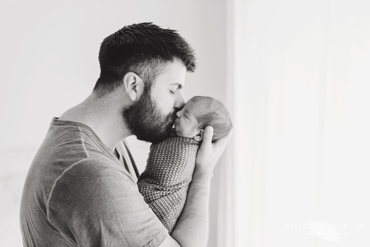 Black and white of daddy kissing newborn baby boy