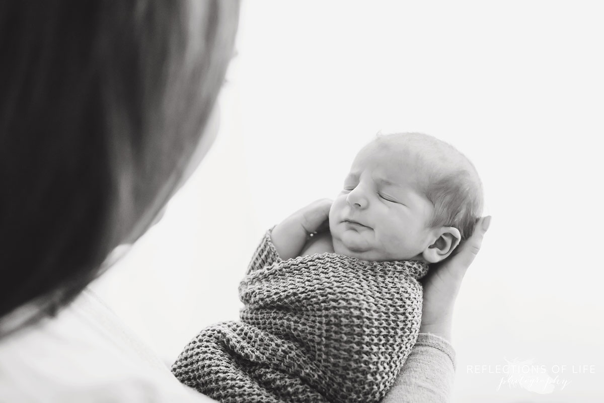 Mom looks down at newborn baby boy