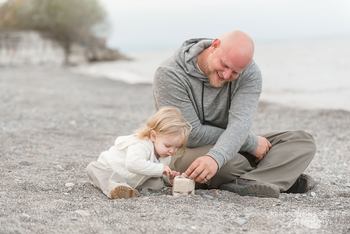 Father and son smiling as they build a tower out of rocks at the beach in Grimsby Ontario.jpg