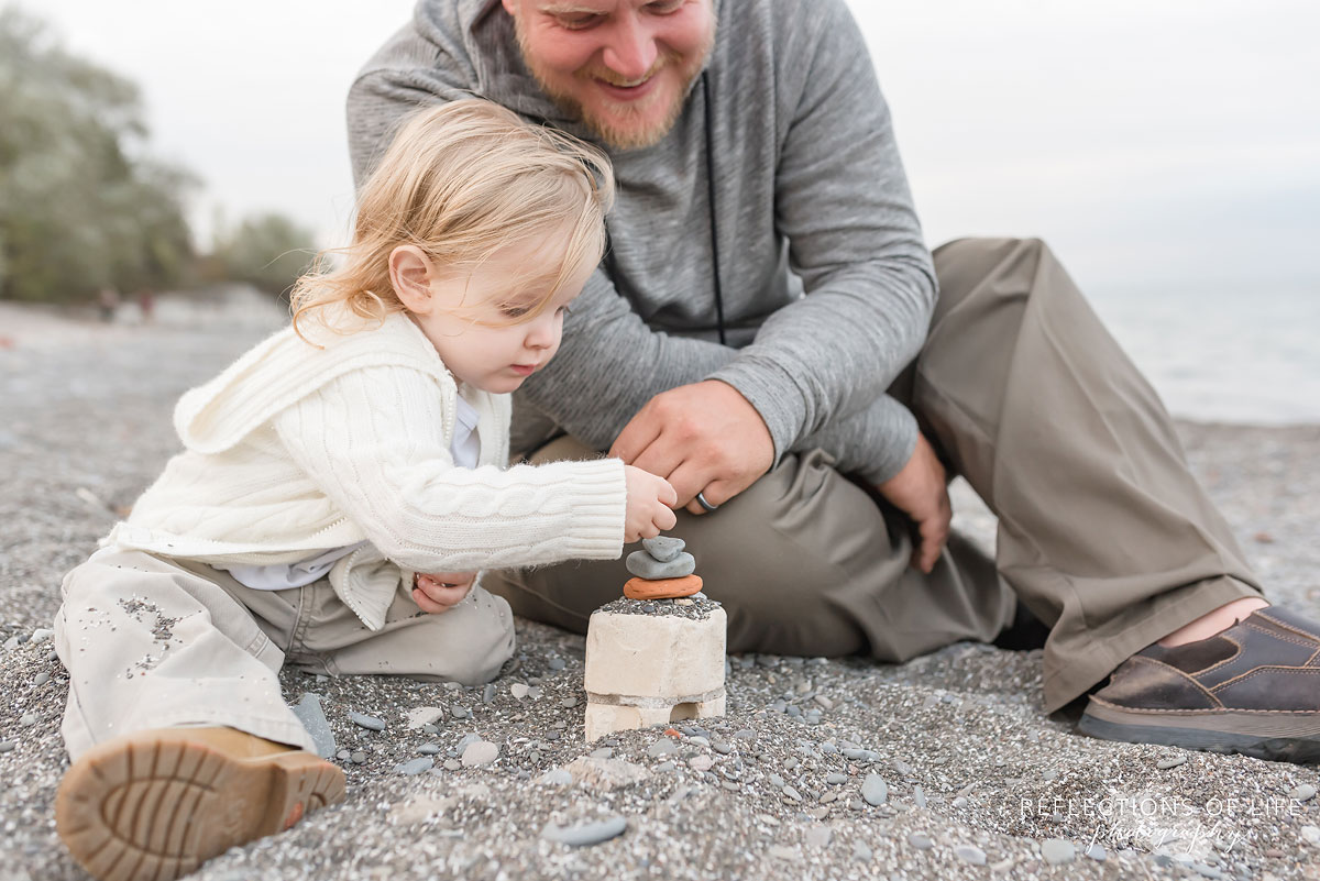 Father and toddler son happy to build a rock tower together in Niagara Ontario Canada.jpg