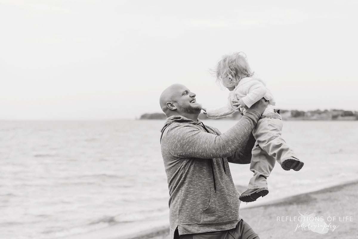Black and white photo of father holding toddler son up in the air.jpg