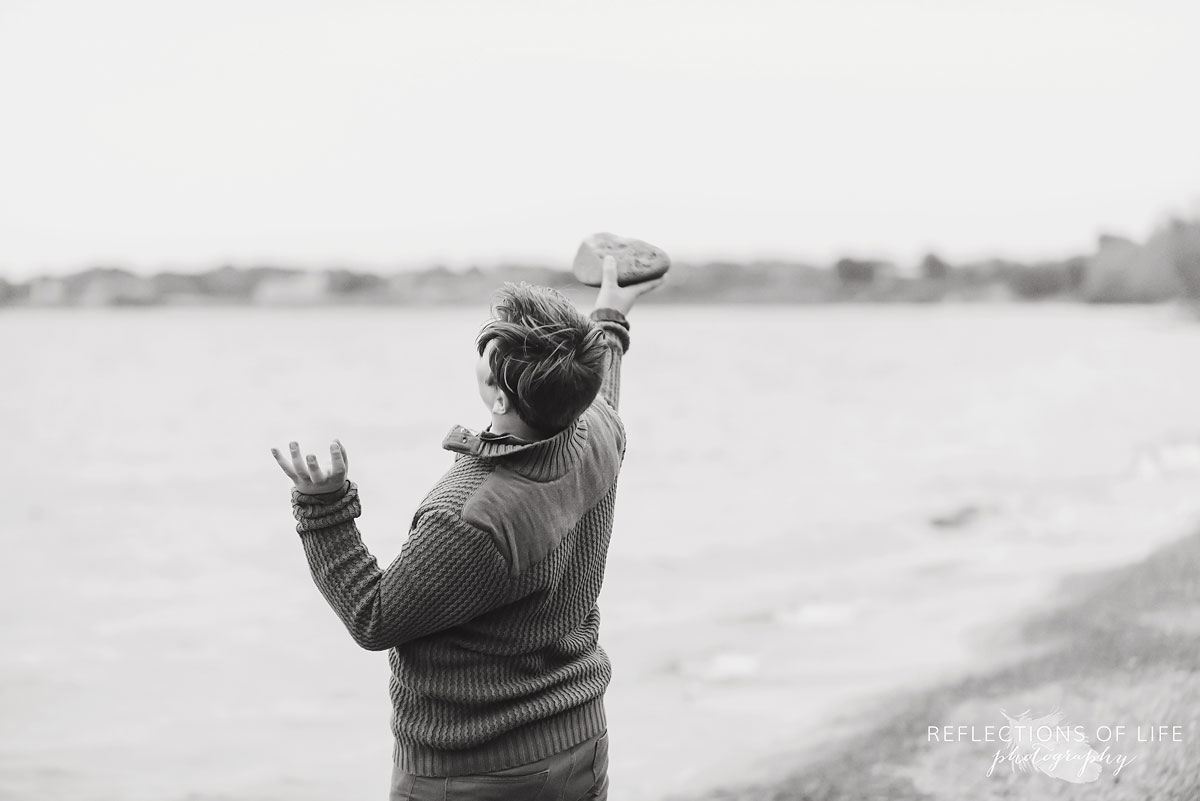 Teenage boy throwing rocks into the water at Grimsby Beach in Ontario.jpg