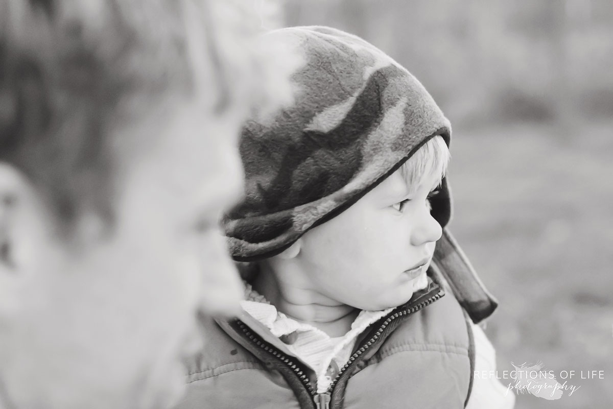 Little boy looks off into the distance in Canadian winter