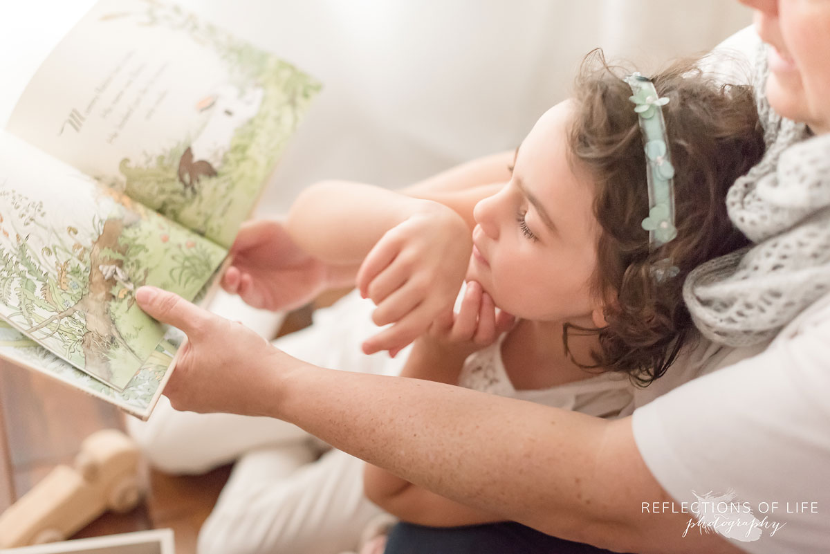 daughter reading in mothers lap