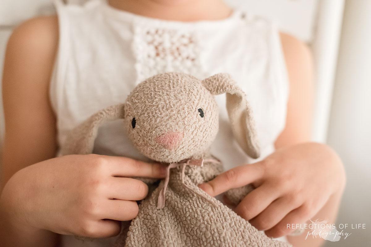 young girl holding stuffed bunny