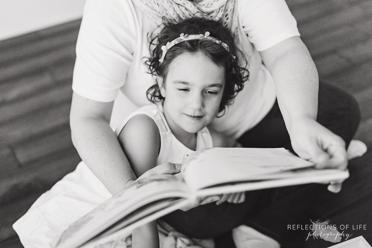 mother reading to daughter black and white