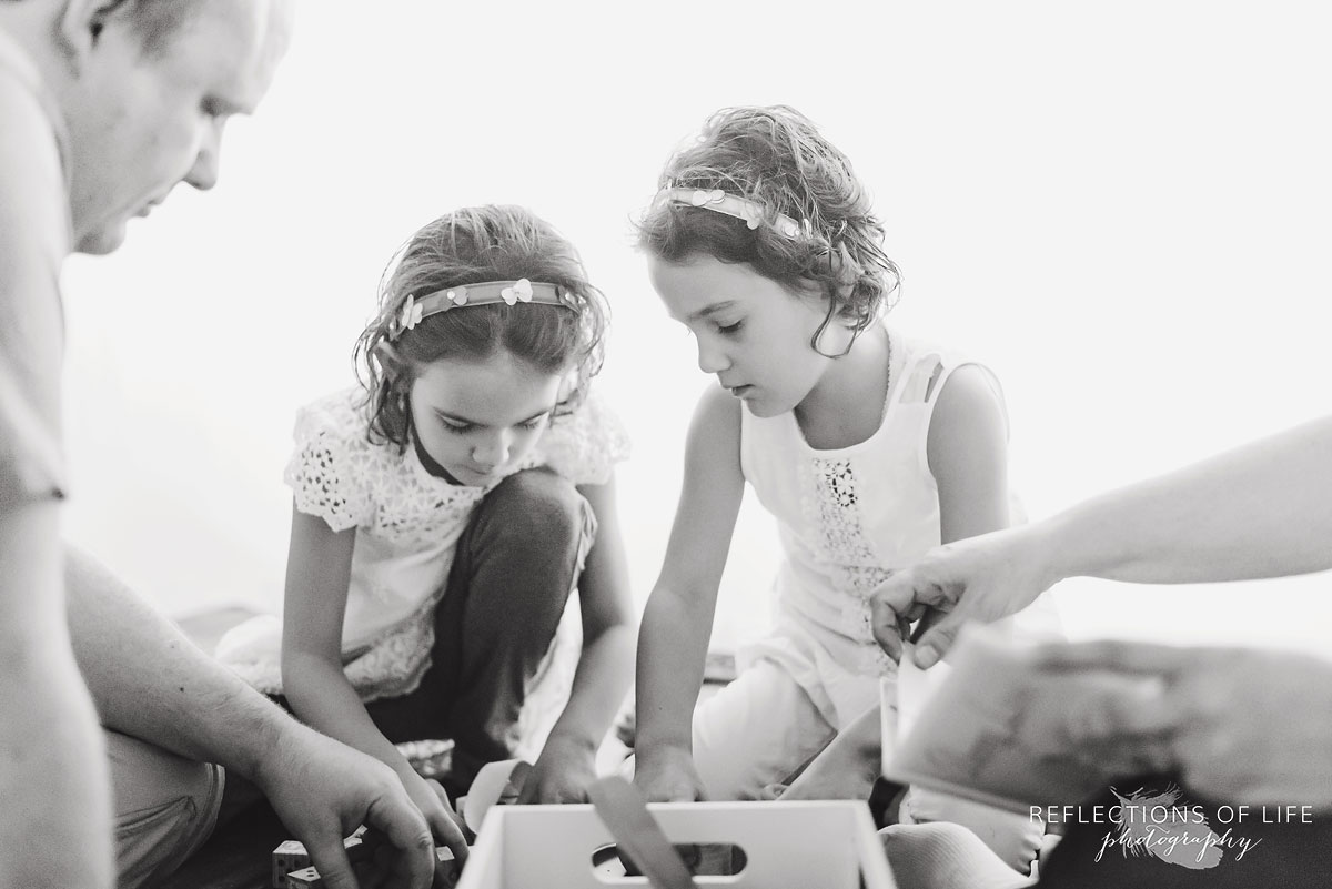 twin girls playing with father black and white