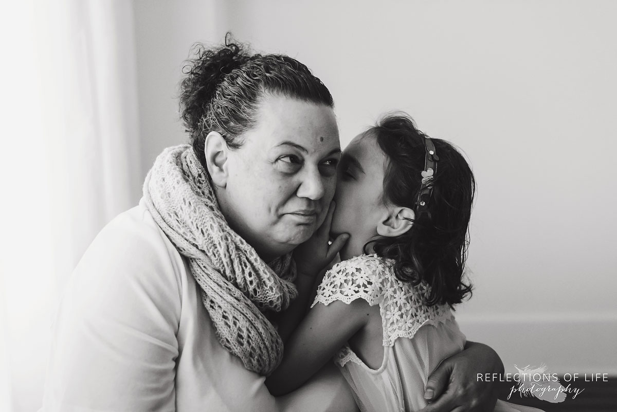 daughter giving mother a kiss black and white