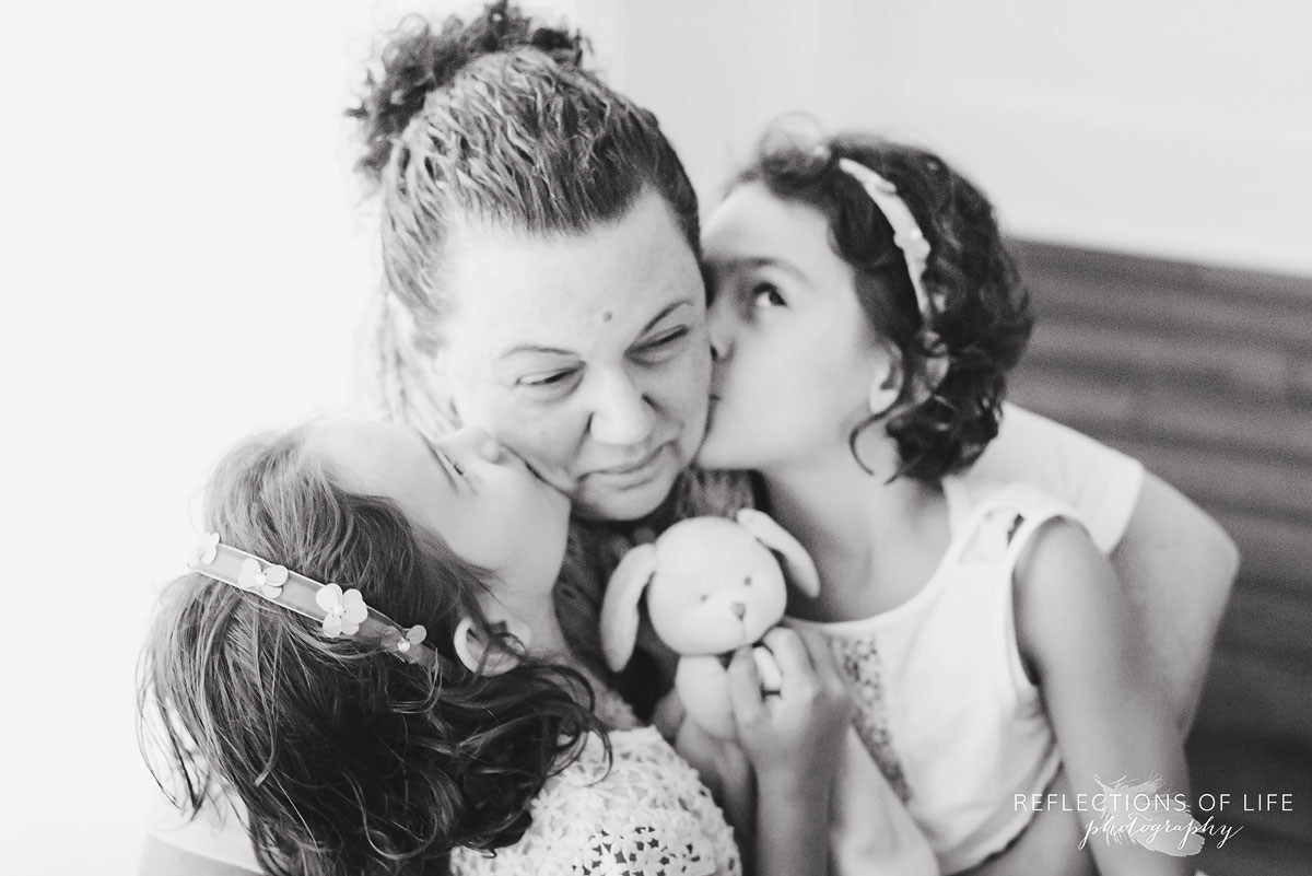 twin sisters kissing mother on the cheeks black and white