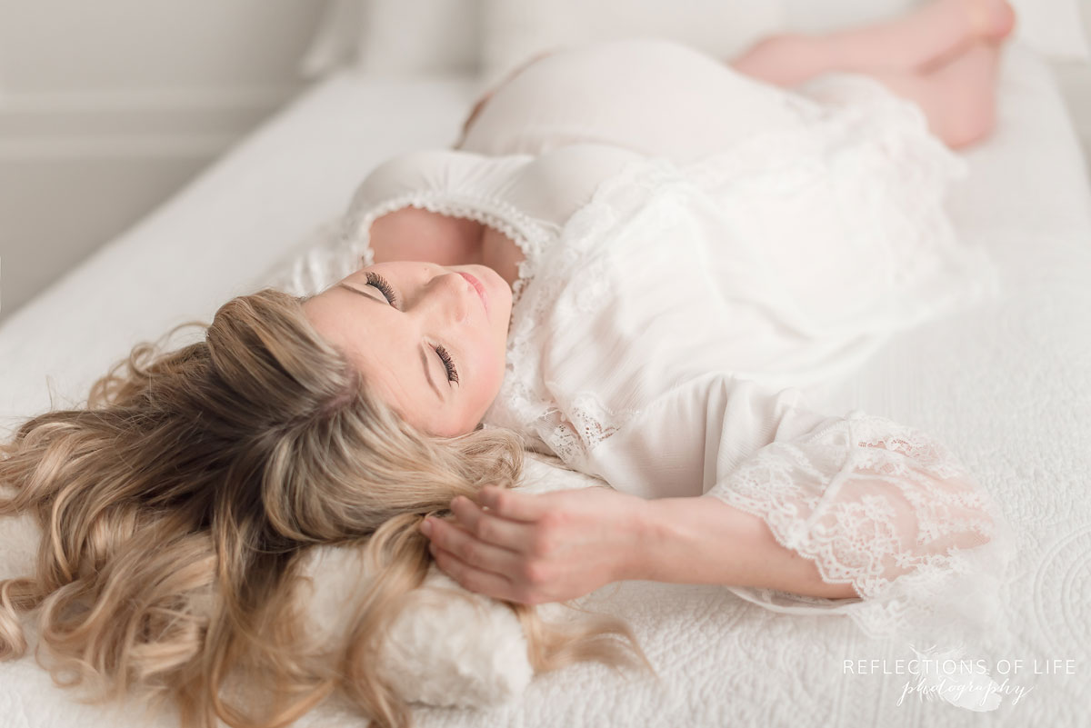 blonde pregnant women laying on bed
