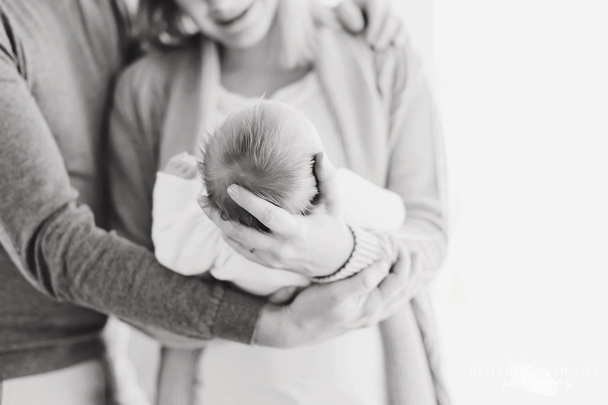mother and father holding newborn black and white