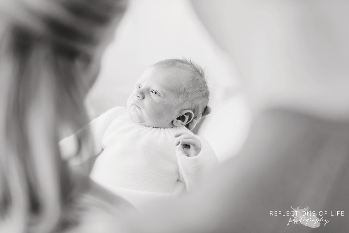 mother looking at newborn black and white