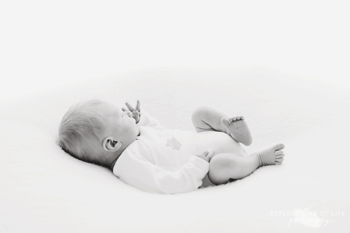 black in white newborn laying on bed