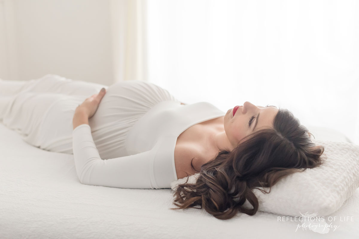 pregnant mother to be laying on back on bed