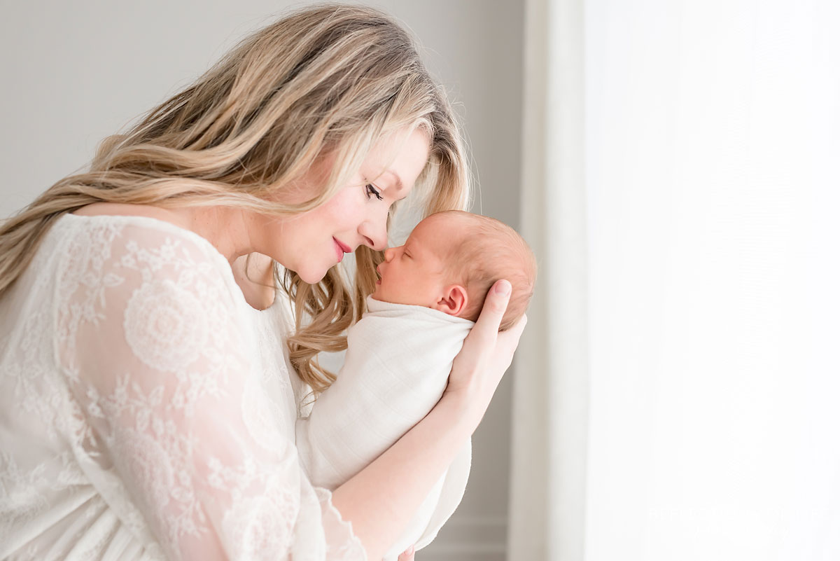 mother holding newborn baby girl touching noses