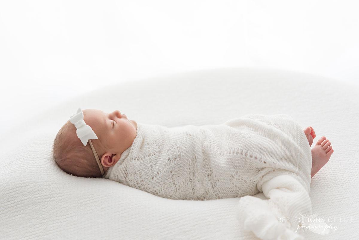 newborn baby laying on bed wearing headband