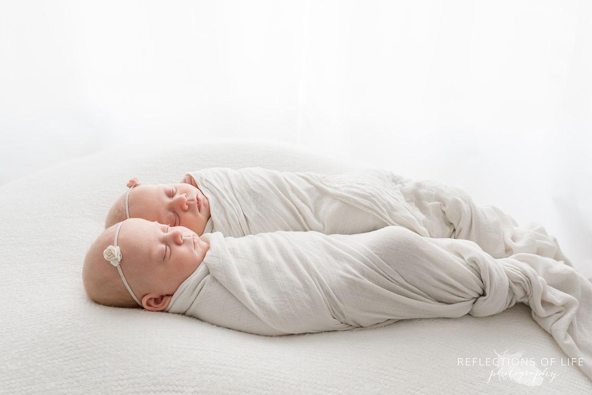 newborn twin baby girls laying together