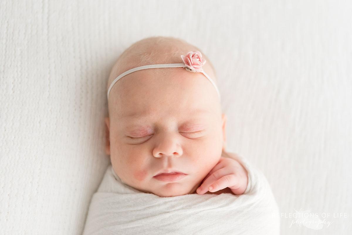 newborn baby girl sleeping wearing headband
