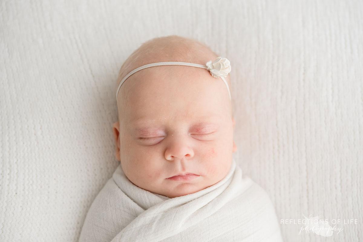 newborn baby girl wearing white headband