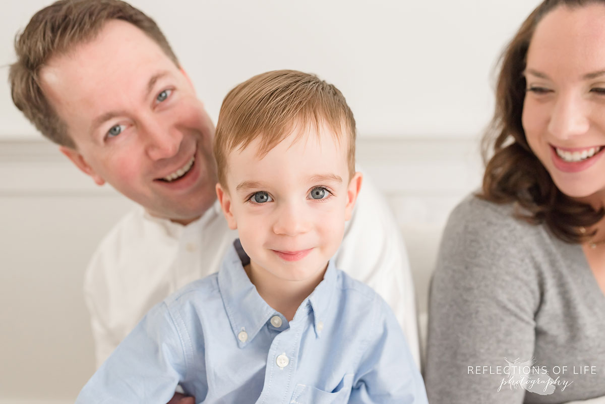 little boy in his parents arms smiling at the camera