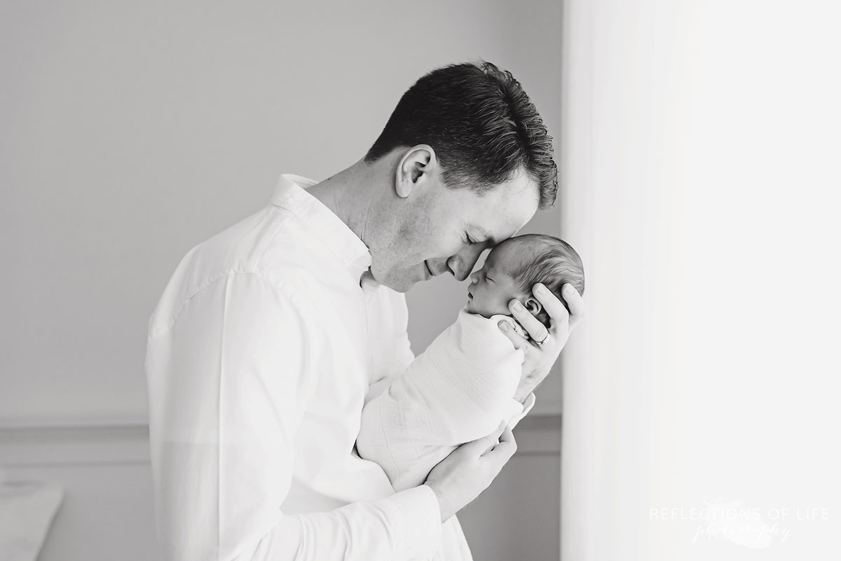 proud daddy resting his head on his gorgeous newborn baby girl