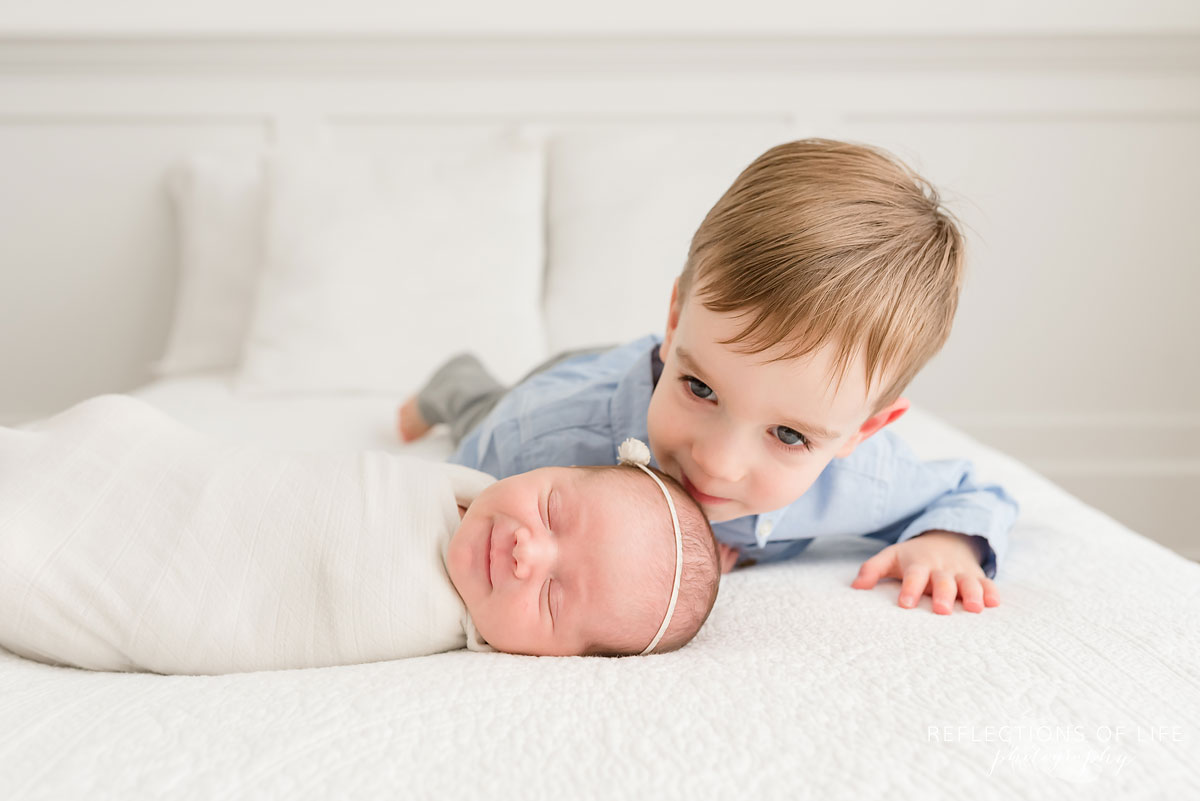 newborn baby girl smiling as her older brother kisses her on the head