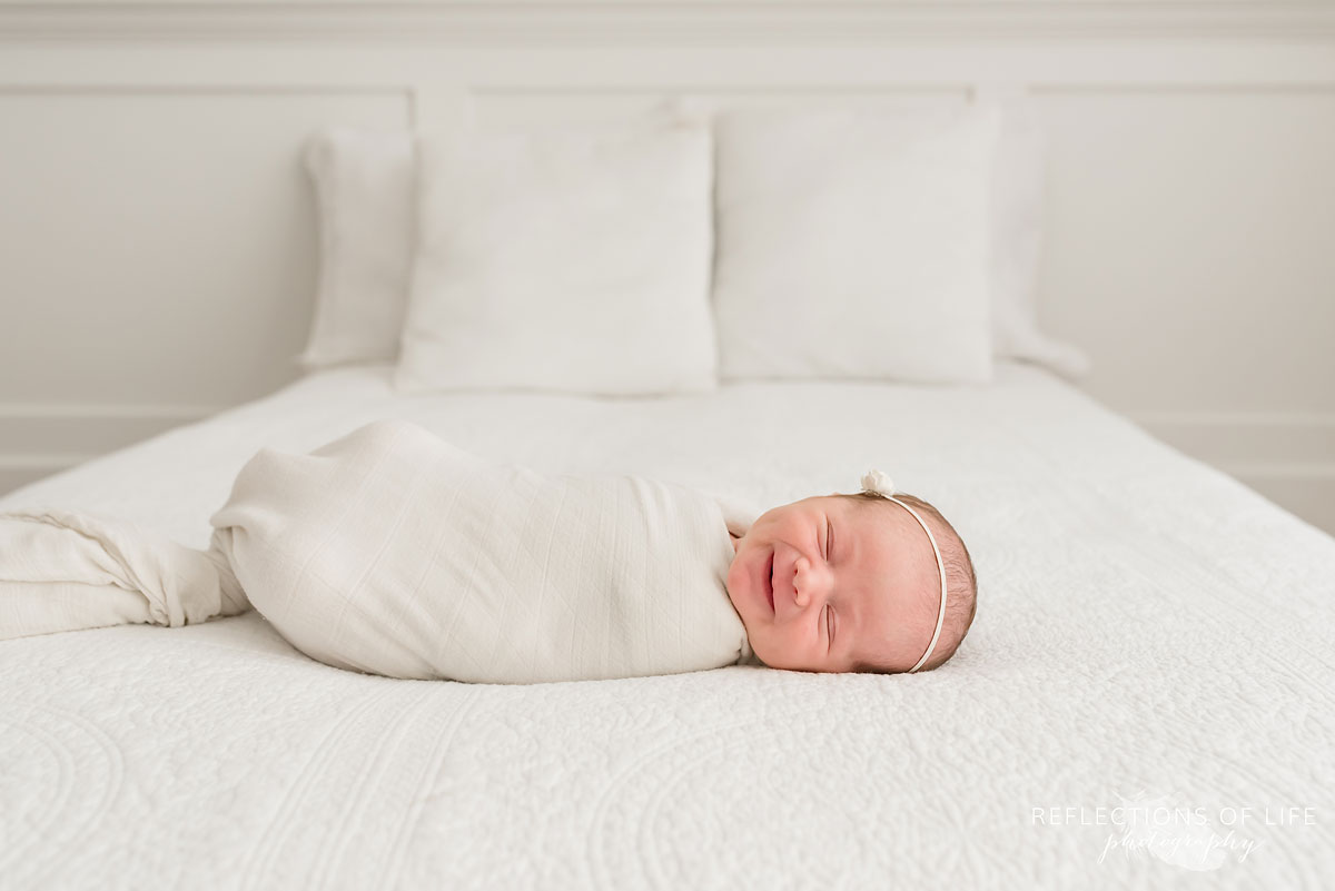newborn baby girl smiling on the bed